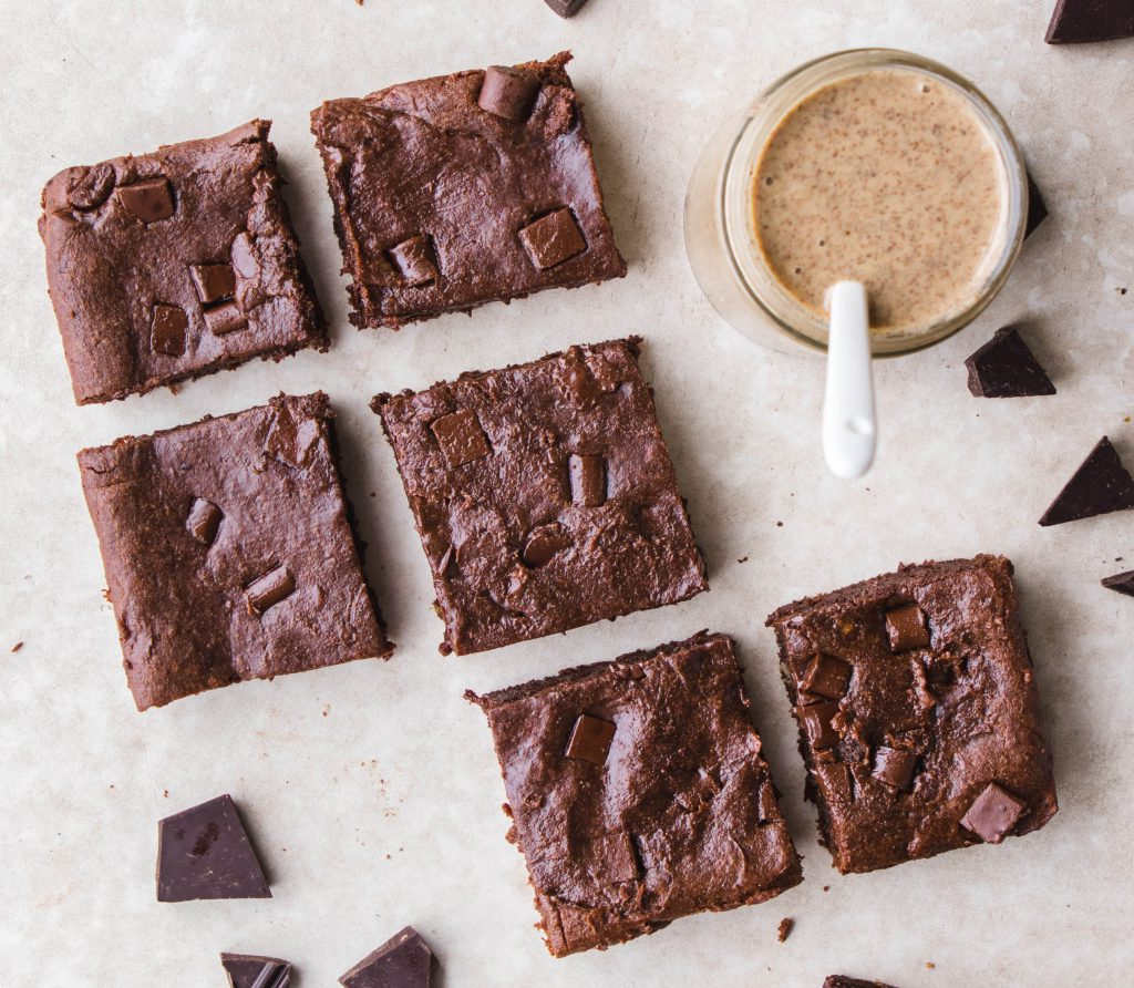 Almond butter brownies in slices with almond butter jar.