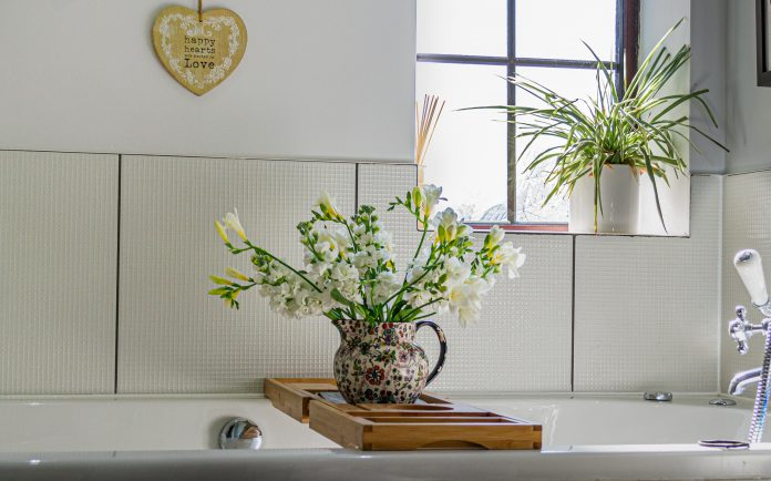 Jug of flowers over bath and house plant on window sill.